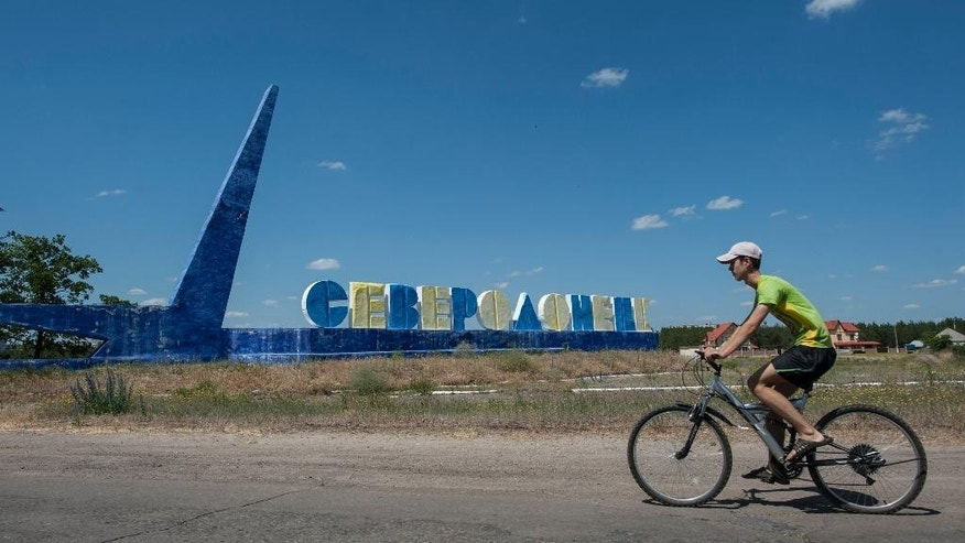 "FOR STORY UKRAINE NO MAN'S LANDS - In this photo taken on Thursday, June  11, 2015, a boy rides a bicycle past the sign reading ""Severodonetsk"" in the town of Severodonetsk, Luhansk region, eastern Ukraine. Pro-Russian sympathies have historically been strong in a region where Ukrainian identity has tended to be much weaker than elsewhere in the country. (AP Photo/Evgeniy Maloletka)"