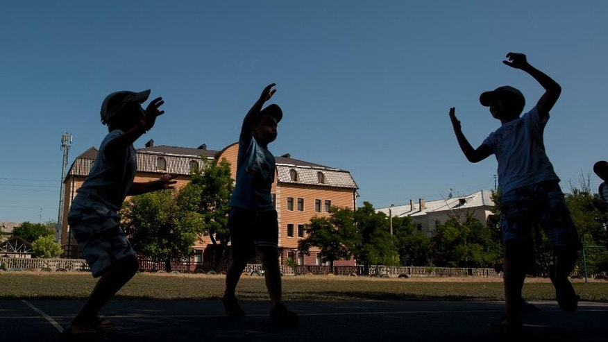 FOR STORY UKRAINE NO MAN'S LANDS - In this photo taken on Thursday, June  11, 2015, local children play volleyball in the town of Severodonetsk, Luhansk region, eastern Ukraine.  The plinth once topped by the statue of Vladimir Lenin, the Bolshevik leader reviled by Ukrainian nationalists, stands empty in Severodonetsk, but there is still an abiding fondness among many elderly people for the communist era. (AP Photo/Evgeniy Maloletka)