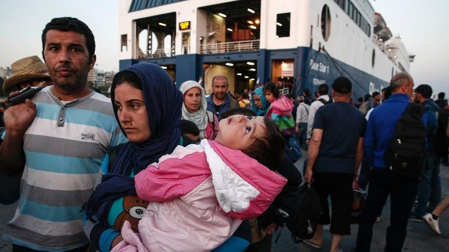 Migrants, who have reached the Greek eastern Aegean islands after crossing the Greek-Turkish sea borderline, wait outside a passenger ship following their disembarkation at the port of Piraeus, near Athens, Greece, on Sunday, June 14, 2015. An emergency European Union plan to help Italy and Greece manage thousands of migrants crossing the Mediterranean could be vastly watered down next week, diplomats said Friday.  (AP Photo/Yorgos Karahalis)