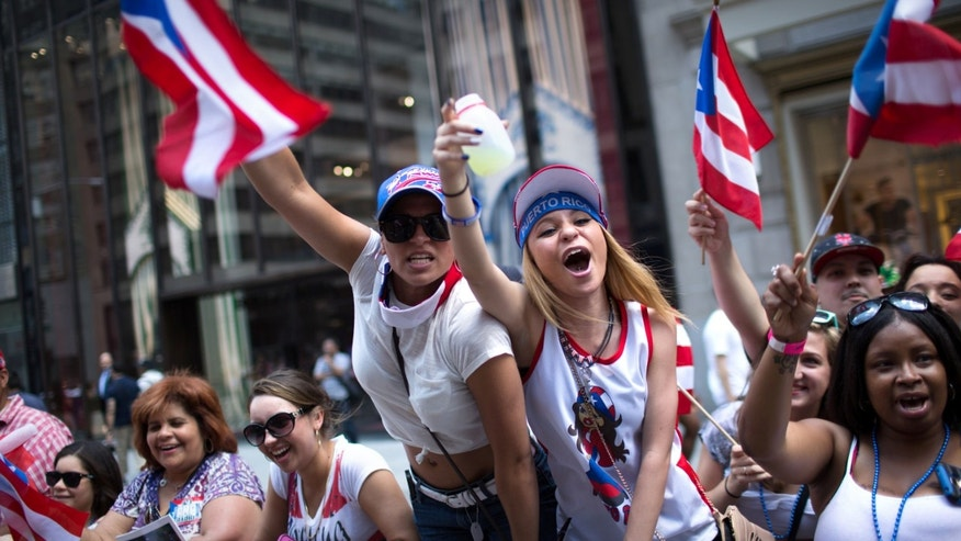 Arsenia Fuentes, center left, and Sarah Dones, center right, cheer for a passing float as the annual National Puerto Rican Day Parade makes its way up New York's Fifth Ave., Sunday, June 14, 2015. Hundreds of thousands of people turned out for the parade which celebrates the heritage and identity of Puerto Ricans living in New York. (AP Photo/Kevin Hagen)