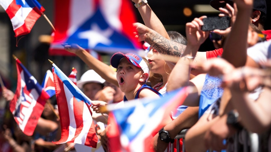 Jaydden Garcia, 8, center, cheers as the annual National Puerto Rican Day Parade makes its way up New York's Fifth Ave., Sunday, June 14, 2015. Hundreds of thousands of people turned out for the parade which celebrates the heritage and identity of Puerto Ricans living in New York. (AP Photo/Kevin Hagen)