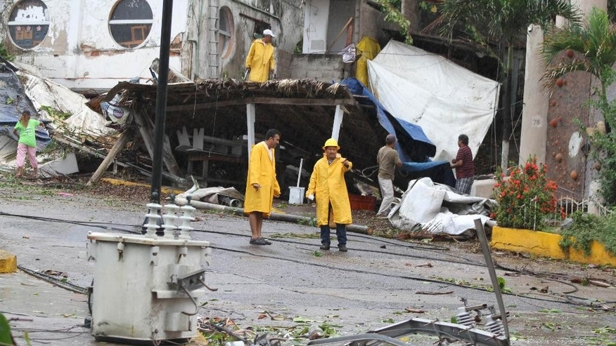 Utility workers survey the damage caused by winds and rains from hurricane Carlos in the Pacific resort city of Acapulco, Mexico, Sunday, June 14, 2015. Carlos lost its brief hurricane status on Sunday as it weakened while sitting nearly stationary some 65 miles (110 kilometers) southwest of Acapulco, according to the U.S. National Hurricane Center in Miami, which measured top sustained winds at 65 mph (110 kph) Sunday afternoon. (AP Photo/Bernandino Hernandez)