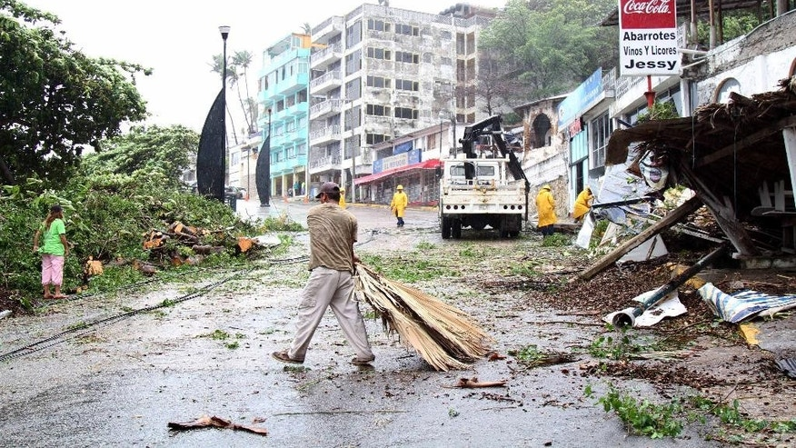 A man clears debris as utility workers prepare to replace a light pole that was brought down by winds and rains from hurricane Carlos in the Pacific resort city of Acapulco, Mexico, Sunday, June 14, 2015. Carlos lost its brief hurricane status on Sunday as it weakened while sitting nearly stationary some 65 miles (110 kilometers) southwest of Acapulco, according to the U.S. National Hurricane Center in Miami, which measured top sustained winds at 65 mph (110 kph) Sunday afternoon. (AP Photo/Bernandino Hernandez)