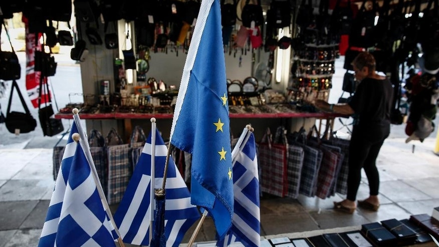 "A woman adjusts items beside the flags of European Union flag, center top, and Greece, outside a kiosk in Piraeus, near Athens, Greece, on Sunday, June 14, 2015.  A government official says Greek Prime Minister Alexis Tsipras has told senior aides to ""forget about elections or a referendum,"" whatever the outcome of the country's talks with creditors. (AP Photo/Yorgos Karahalis)"