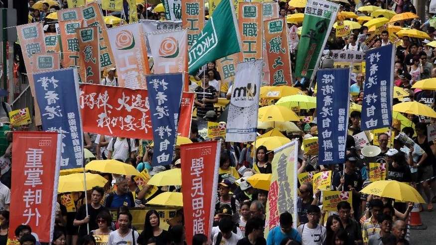 People march in a downtown street to support for a veto of the government's electoral reform package in Hong Kong, Sunday, June 14, 2015. The rally was held ahead of a crucial vote by lawmakers on Beijing-backed election reforms that sparked huge street protests last year. (AP Photo/Vincent Yu)