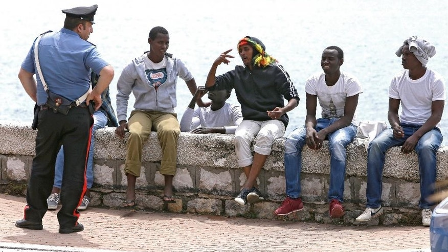 An Italian policeman speaks with migrants sitting at the Franco-Italian border near Menton, southeastern France, Sunday, June 14, 2015. Some 150 migrants, principally from Eritrea and Sudan, attempted to cross the border from Italy and have been blocked by French and Italian gendarmes. (AP Photo/Lionel Cironneau)