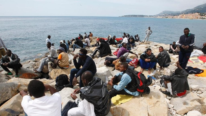 Migrants gather at the Franco-Italian border near Menton, southeastern France, Sunday, June 14, 2015. Some 150 migrants, principally from Eritrea and Sudan, attempted to cross the border from Italy and have been blocked by French and Italian gendarmes. (AP Photo/Lionel Cironneau)