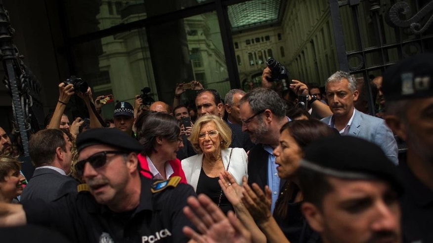 Madrid's new Mayor and member of Ahora Madrid (Madrid Now) party Manuela Carmena, center, meets the crowd in Madrid, Spain, Saturday, June 13, 2015. Spain's biggest cities, Madrid and Barcelona, are expected to swear in far-left mayors Saturday in one of the nation's biggest political upheavals in years. The radical leaders promise to cut their own salaries, halt homeowner evictions and eliminate perks enjoyed by the rich and famous. The leadership change comes weeks after Spain's two largest traditional parties were punished in nationwide local elections by voters groaning under the weight of austerity measures and repulsed by a string of corruption scandals. (AP Photo/Andres Kudacki)