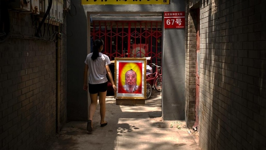 In this Saturday, June 13, 2015 photo, a girl walks past a sign advertising the services of a fortune teller in an alley near the Lama Temple in Beijing. The former Chinese security czar recently convicted of leaking state secrets did not pass classified documents to a foreign spy or a political rival. Rather, Zhou Yongkang, a former member of the all-powerful Standing Committee of the ruling Communist Party's Politburo, shared the documents with his qigong master, who claims supernatural abilities, according to a verdict made public last week and which also convicted Zhou of massive corruption. It's the latest example of a twisted relationship between the leadership of the party, which nominally espouses atheism, and spirituality. The sign at top advertises a shop providing Buddhist supplies. (AP Photo/Mark Schiefelbein)