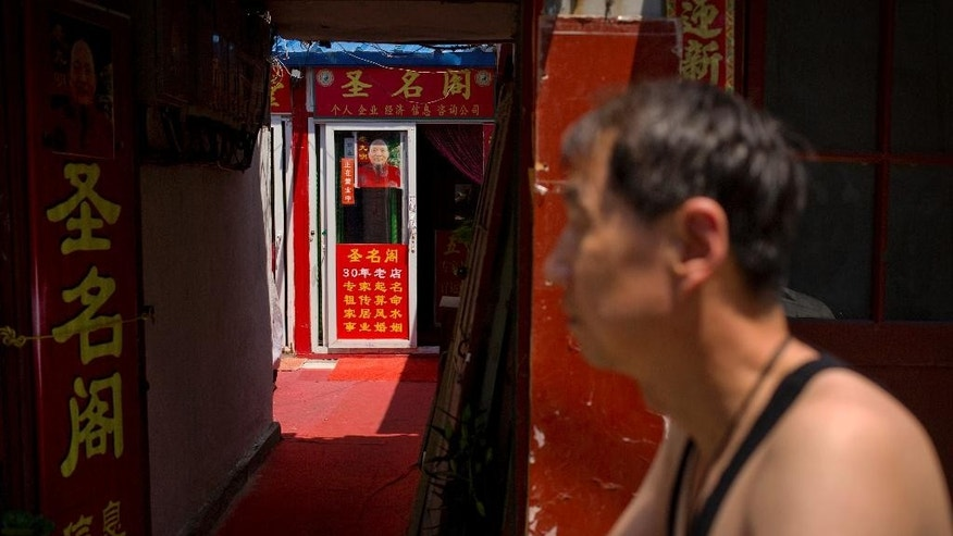 In this Saturday, June 13, 2015 photo, a man walks past signs advertising the services of a fortune teller in an alley near the Lama Temple in Beijing. The Chinese government announced Thursday, June 11, 2015 that former security czar Zhou Yongkang had been convicted of charges including passing secret documents to his qigong master, and Zhou is one of a number of senior officials in officially atheist China who are said to have sought help and advice from religious and spiritual advisers. The sign at left advertises the fortune teller's services in providing auspicious names. (AP Photo/Mark Schiefelbein)