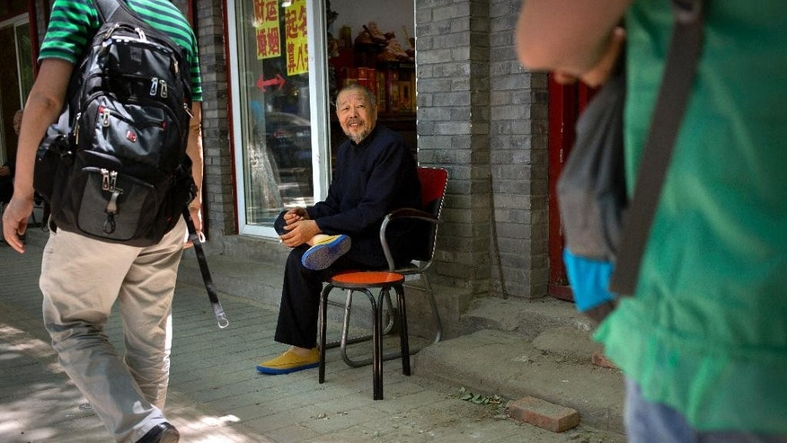 In this Saturday, June 13, 2015 file photo, a fortune teller, center, waits for clients outside his shop on a street near the Lama Temple in Beijing. The Chinese government announced Thursday, June 11, 2015 that former security czar Zhou Yongkang had been convicted of charges including passing secret documents to his qigong master, and Zhou is one of a number of senior officials in officially atheist China who are said to have sought help and advice from religious and spiritual advisers. (AP Photo/Mark Schiefelbein)