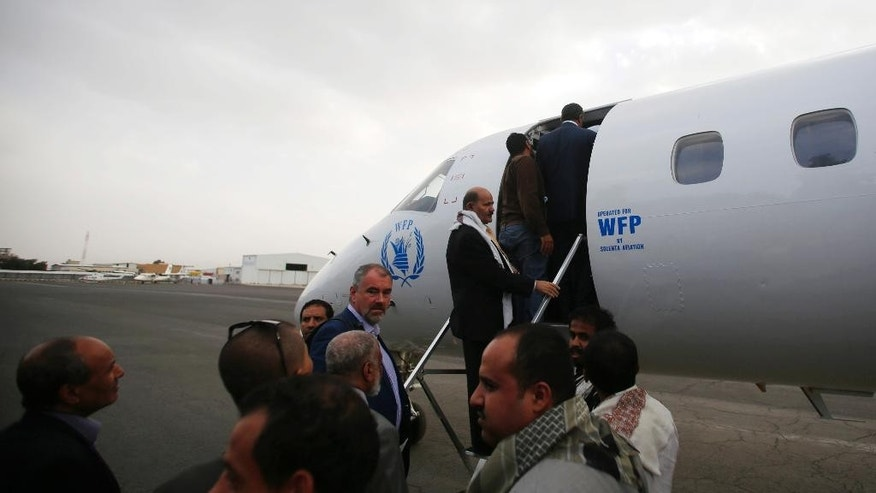 Yemeni political groups, including Shiite rebels known as Houthis, get on an airplane for Geneva for U.N.-led peace talks at the airport in Sanaa, Yemen, Sunday, June 14, 2015. The talks are slated to be first substantive meetings by all parties involved in the conflict. (AP Photo/Hani Mohammed)