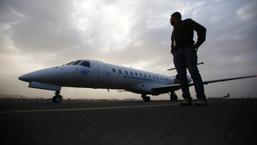 A man stands next to a plane as Yemeni political groups, including Shiite rebels known as Houthis, travel to Geneva for U.N.-led peace talks at the airport in Sanaa, Yemen, Sunday, June 14, 2015. The talks are slated to be first substantive meetings by all parties involved in the conflict. (AP Photo/Hani Mohammed)