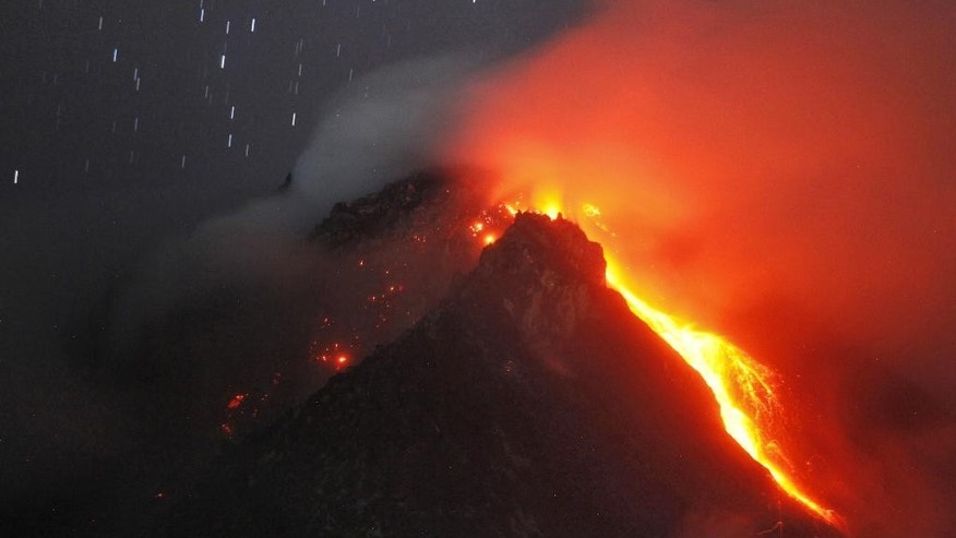 In this photo taken with slow shutter speed, hot lava flows from the crater of Mount Sinabung as seen from Tiga Serangkai, North Sumatra, Indonesia, early Monday, June 15, 2015. Authorities have been closely monitoring the 2,460-meter (8,070-foot) -high volcano since June 2 when its status was raised to the highest alert level due to the growing size of its lava dome. (AP Photo/Binsar Bakkara)