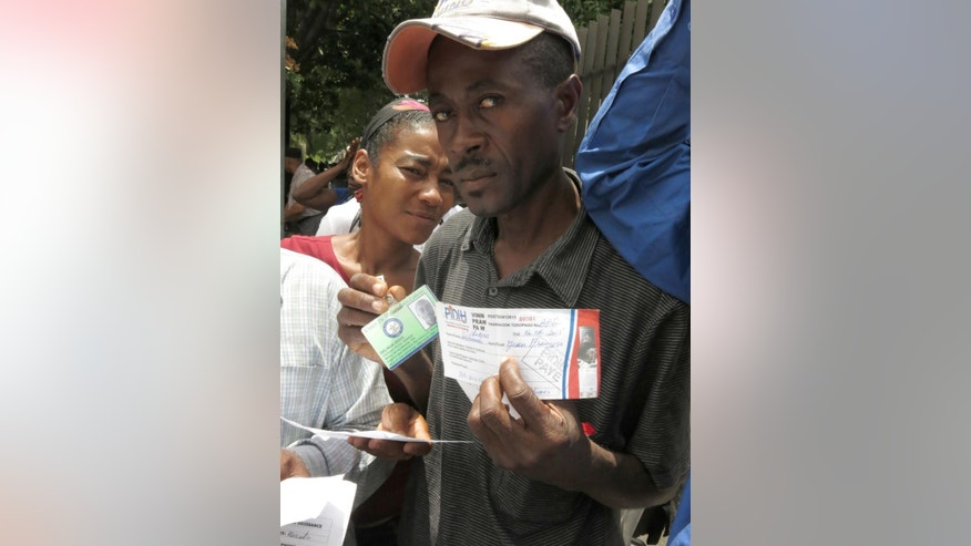 Delinua Dovil Jean Francois, right, shows the supporting documents that proves that he did the paperwork for obtaining his Haitian identity card, in order to apply for a temporary resident permit in the Dominican Republic, in Santo Domingo, Dominican Republic, Monday, June 15, 2015. Hundreds of Haitians are waiting in long lines throughout the Dominican Republic trying to secure legal residency as they face the threat of deportation. The government has given non-citizens until Tuesday to register under an initiative aimed at regulating the flow of migrants from neighboring Haiti. (AP Photo/Ezequiel Abiu Lopez)