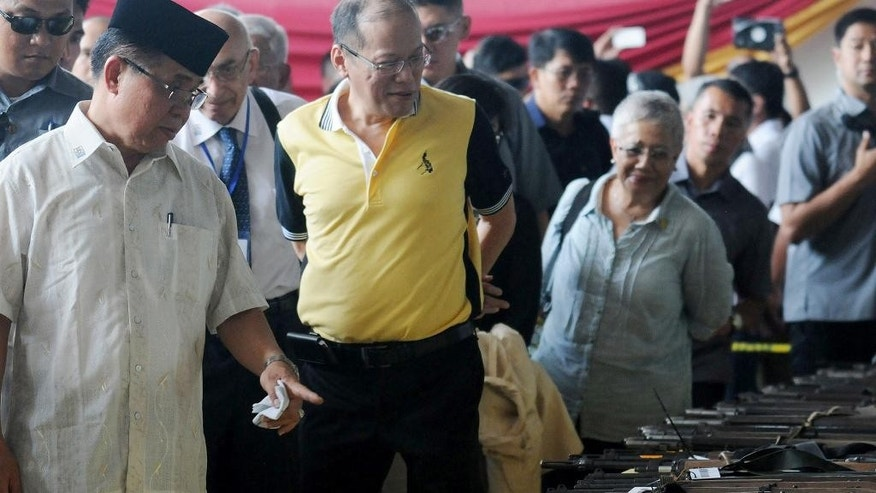 Philippines President Benigno Aquino III, center, is briefed by Al Haj Murad Ebrahim, left, the leader of the 11,000-strong Moro Islamic Liberation Front, as he witnesses the handover of 75 assault weapons, including mortar and rocket launchers, by guerrillas in a symbolic decommissioning ceremony Tuesday, June 16, 2015, near a southern rebel stronghold in Sultan Kudarat, Maguindanao province, in southern Philippines. The largest Muslim rebel group in the Philippines handed over dozens of assault weapons Tuesday in a symbolic gesture to reinforce a peace pact stalled by a public outcry over the recent killings of dozens of anti-terror police commandos in a fierce battle with insurgents. (AP Photo)