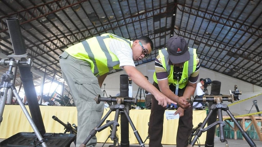 Officials inspect 75 assault weapons, including mortar and rocket launchers, handed over by the 11,000-strong Moro Islamic Liberation Front, in a symbolic decommissioning ceremony Tuesday, June 16, 2015, near a southern rebel stronghold in Sultan Kudarat, Maguindanao province in southern Philippines. The largest Muslim rebel group in the Philippines handed over dozens of assault weapons Tuesday in a symbolic gesture to reinforce a peace pact stalled by a public outcry over the recent killings of dozens of anti-terror police commandos in a fierce battle with insurgents. (AP Photo)
