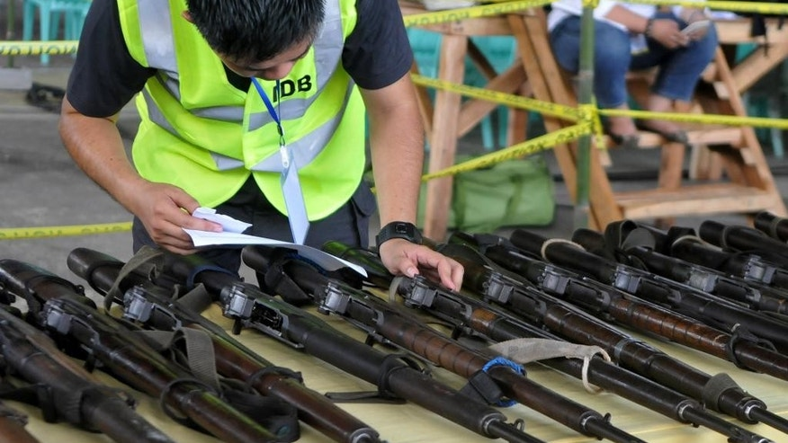 An official inspects assault weapons handed over by the 11,000-strong Moro Islamic Liberation Front in a symbolic decommissioning ceremony Tuesday, June 16, 2015, near a southern rebel stronghold in Sultan Kudarat, Maguindanao province in southern Philippines. The largest Muslim rebel group in the Philippines handed over dozens of assault weapons Tuesday in a symbolic gesture to reinforce a peace pact stalled by a public outcry over the recent killings of dozens of anti-terror police commandos in a fierce battle with insurgents. (AP Photo)
