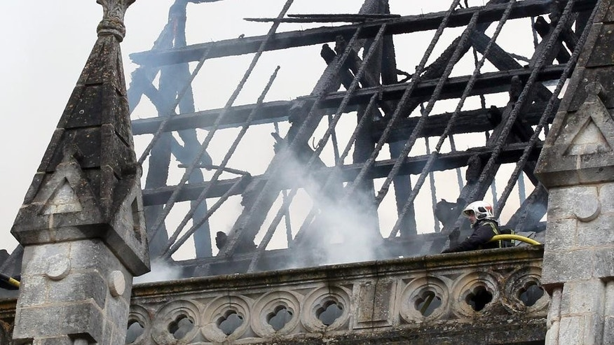 A firefighter hoses water to put out the fire in a basilica in Nantes, western France, Monday, June 15, 2015. A fire is ravaging a 19th century basilica in the western French city of Nantes, and has left just a shell of the rooftop. The fire began just after morning Mass on Monday and everyone inside was quickly evacuated, the Rev. Benoit Bertrand of the Nantes diocese told BFM television. (AP Photo/Laetitia Notarianni)