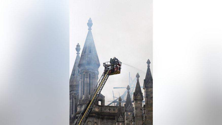 Firefighters hose water to put out the fire in a basilica in Nantes, western France, Monday, June 15, 2015. A fire is ravaging a 19th century basilica in the western French city of Nantes, and has left just a shell of the rooftop. The fire began just after morning Mass on Monday and everyone inside was quickly evacuated, the Rev. Benoit Bertrand of the Nantes diocese told BFM television. (AP Photo/Laetitia Notarianni)