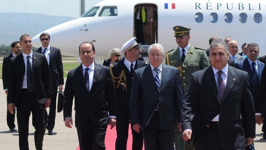 French President Francois Hollande, center left , and Algerian President of the Council of the Nation Abdelkader Bensalah, centre, walk on the red carpet at Houari Boumediene airport in Algiers, Algeria, Monday, June 15, 2015. Hollande made a fleeting visit to Algiers for a few hours to meet his Algerian counterpart Abdelaziz Bouteflika. (AP Photo/Sidali Djarboub)