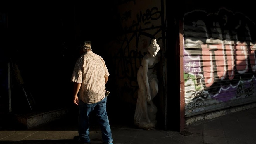 A man enters an antique shop in central Athens, on Monday, June 15, 2015. The European Commission said Sunday that weekend talks to find common ground between international creditors and Greece were unsuccessful and left a wide rift that needs to be closed within two weeks to avoid a possible Greek default.(AP Photo/Petros Giannakouris)