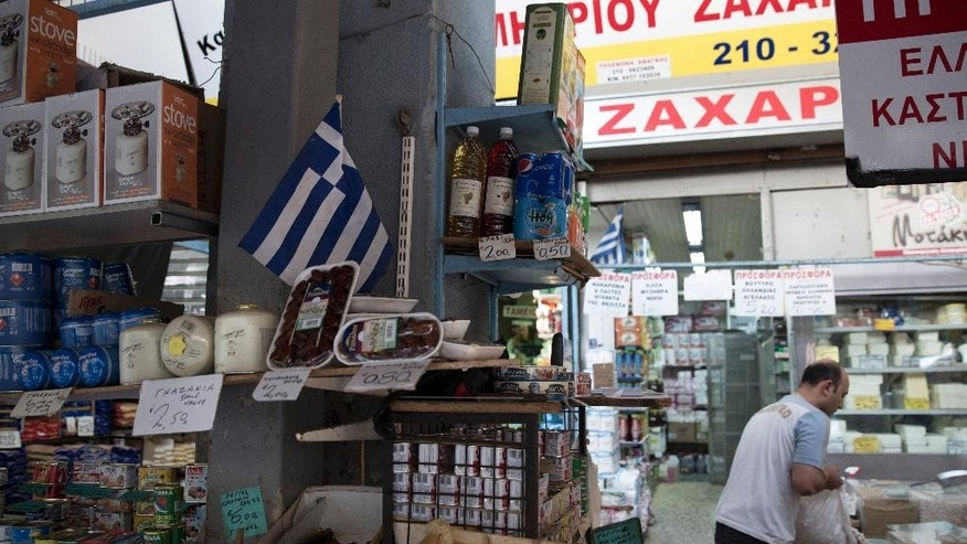 A Greek flag is seen in a mini market in central Athens on Monday, June 15, 2015. The European Commission said Sunday that weekend talks to find common ground between international creditors and Greece were unsuccessful and left a wide rift that needs to be closed within two weeks to avoid a possible Greek default.(AP Photo/Petros Giannakouris)