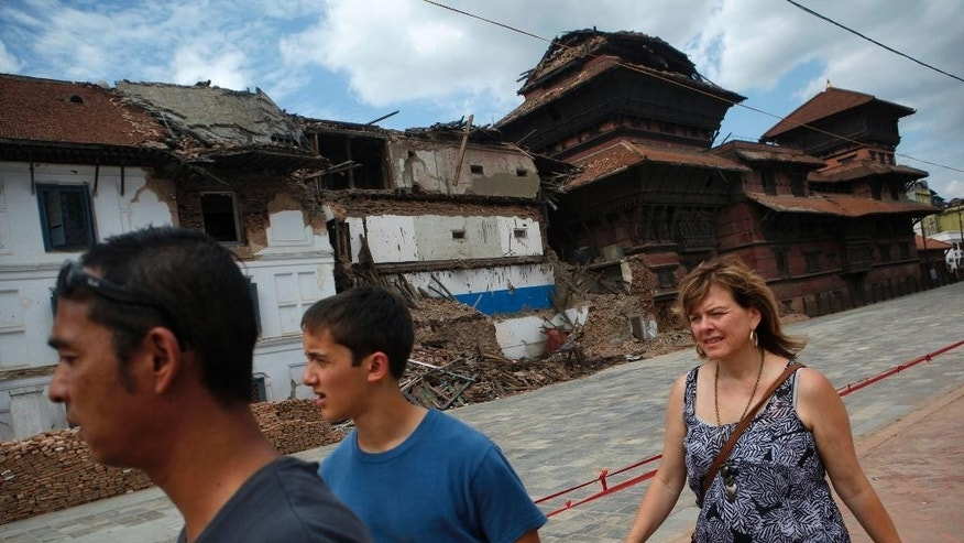 Tourist walk near damaged buildings at Basantapur Durbar Square in Kathmandu, Nepal, Monday, June 15, 2015. Nepal on Monday reopened most of the cultural heritage sites that were damaged in a pair of devastating earthquakes, hoping to lure back foreign tourists. (AP Photo/Niranjan Shrestha)