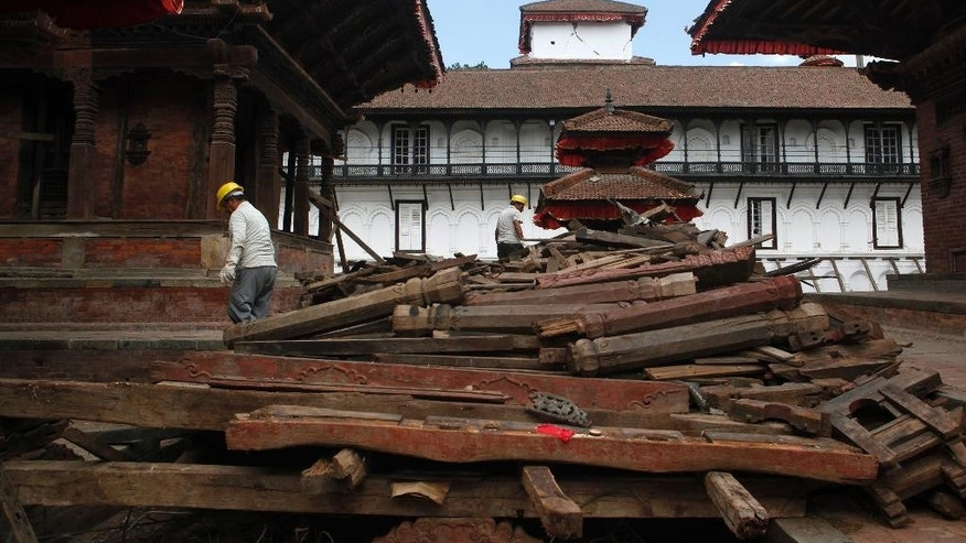 Nepalese construction workers work on a collapsed building near damaged Basantapur Durbar Square in Kathmandu, Nepal, Monday, June 15, 2015. Nepal on Monday reopened most of the cultural heritage sites that were damaged in a pair of devastating earthquakes, hoping to lure back foreign tourists. (AP Photo/Niranjan Shrestha)