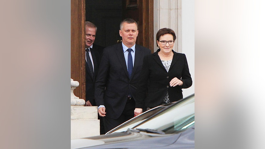 Polish Prime Minister Ewa Kopacz, right,  and her deputy, Defense Minister Tomasz Siemoniak, center, leaving the Belvedere Palace in Warsaw, Poland, on Monday, June 15, 2015 following a meeting with the nation's president, Bronislaw Komorowski, over the appointment of new ministers after four Cabinet members resigned last week over last year's taping scandal. The names of the  new ministers are to be announced later Monday.(AP Photo/Czarek Sokolowski)