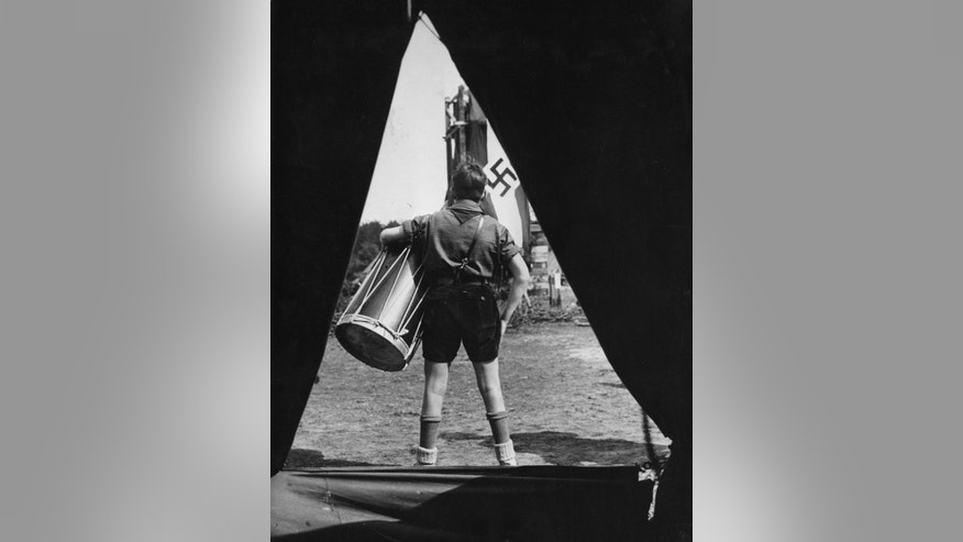 EMBARGOED 19 GMT - FILE - In this undated file photo from the 1930ies a member of the Hitlerjugend - HJ (Hitler Youth) wearing his uniform holds a big drum as he stands in front of a tent in a camp looking at a  flag of the National Socialists with a swastika on it. Anti-Semitic propaganda had a life-long effect on German children schooled during the Nazi period, leaving them far more likely to hold racist ideas than those born earlier and later, according to a study published Monday, June 15, 2015.  The findings indicate that attempts to influence public attitudes are most effective when they target young people, particularly if the message confirms existing beliefs, the authors said.   (AP Photo)