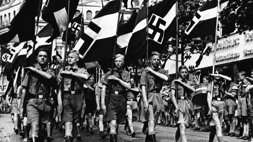 EMBARGOED - 19 GMT FILE - In this Feb. 24, 1936 file photo a group of boys march beneath Nazi standards in Berlin. Anti-Semitic propaganda had a life-long effect on German children schooled during the Nazi period, leaving them far more likely to hold racist ideas than those born earlier and later, according to a study published Monday, June 15, 2015.  The findings indicate that attempts to influence public attitudes are most effective when they target young people, particularly if the message confirms existing beliefs, the authors said.  (AP Photo)