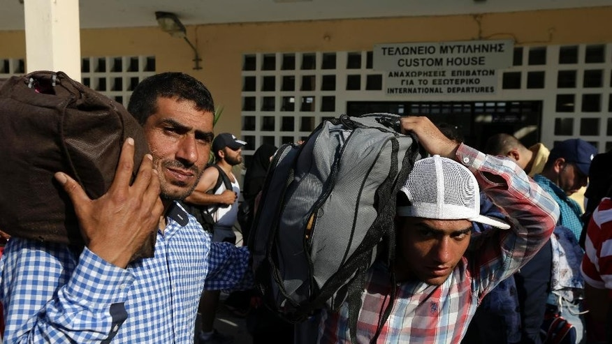 Syrian migrants, who have been stranded for days in the northeastern Greek island of Lesvos, carry their belongings as they wait for travel documents from Greek authorities at the port of Mytilene on Monday, June 15, 2015. An emergency European Union plan to help Italy and Greece manage thousands of migrants crossing the Mediterranean could be vastly watered down on Tuesday, according EU diplomats. During the first five months of 2015, 40,297 migrants arrived in Greece, up from 6,500 in the same period in 2014. Almost all of them have crossed in boats from Turkey. (AP Photo/Thanassis Stavrakis)