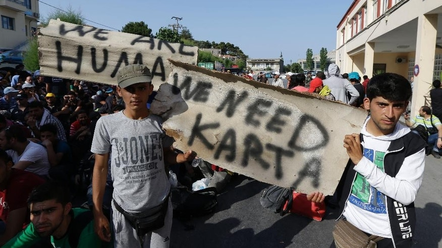 "Syrian migrants who have been stranded for days in the northeastern Greek island of Lesvos, hold a banner that reads: ""We Need Card"", as they gather for travel documents from Greek authorities at the port of Mytilene on Monday, June 15, 2015. An emergency European Union plan to help Italy and Greece manage thousands of migrants crossing the Mediterranean could be vastly watered down on Tuesday, according EU diplomats. During the first five months of 2015, 40,297 migrants arrived in Greece, up from 6,500 in the same period in 2014. Almost all of them have crossed in boats from Turkey. (AP Photo/Thanassis Stavrakis)"