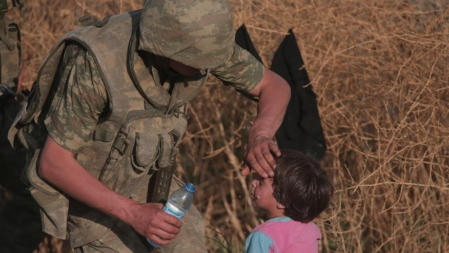 A Turkish soldier splashes water onto a Syrian refugee child after crossing into Turkey from Syria, in Akcakale, Sanliurfa province, southeastern Turkey,  Sunday, June 14, 2015. Thousands of Syrians cut through a border fence and crossed over into Turkey on Sunday, fleeing intense fighting in northern Syria between Kurdish fighters and jihadis.The flow of refugees came as Syrian Kurdish fighters closed in on the outskirts of a strategic Islamic State-held town on the Turkish border. (AP Photo/Lefteris Pitarakis)