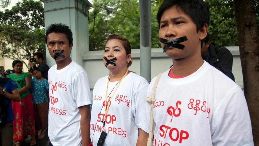 In this July 12, 2014 photo, Myanmar journalists with their mouths sealed with tape, symbolizing the government's crackdown on media, protest outside Myanmar Peace Center in Yangon, Myanmar. Myanmar's government is using threats, harassment and imprisonment to intimidate the media ahead of national elections later this year, Amnesty International said Wednesday, July 17, 2015. (AP Photo/Khin Maung Win)