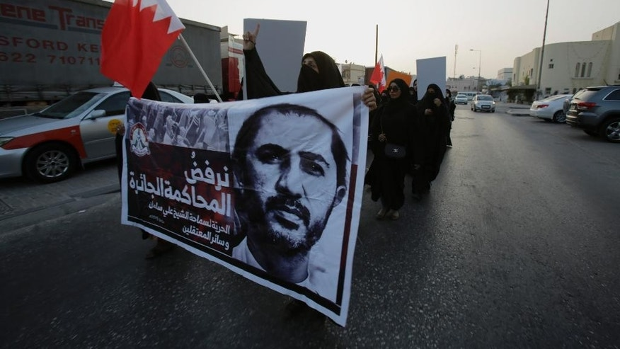 "A small group of Bahraini women carry national flags and a banner showing jailed Shiite cleric Sheikh Ali Salman during a protest against his conviction of insulting the Interior Minister as they march in Manama, Bahrain, Tuesday, June 16, 2015. A court in the Gulf Arab nation of Bahrain sentenced Salman, the country's leading Shiite opposition figure, to four years in prison Tuesday. The banner reads: ""We reject the unjust trial. Freedom to Sheikh Ali Salman and all the prisoners."" (AP Photo/Hasan Jamali)"