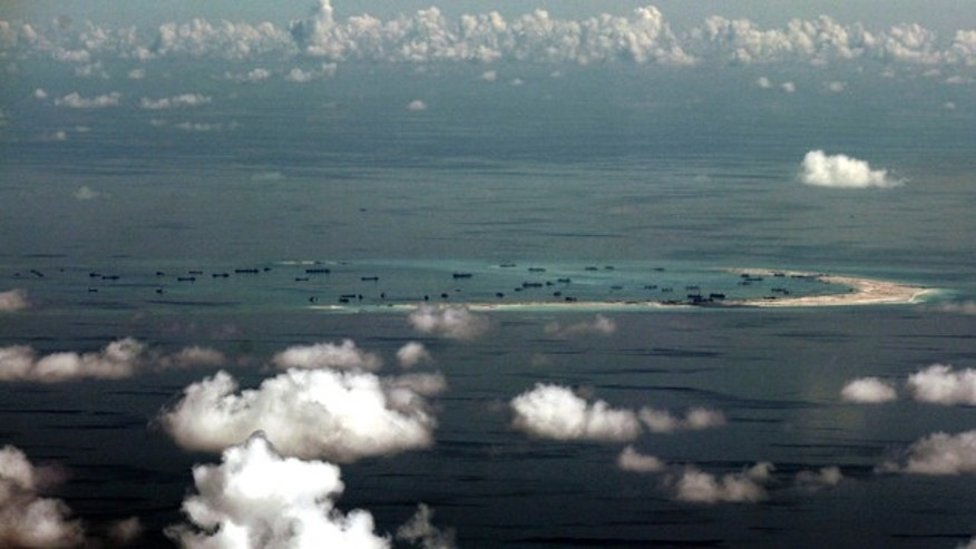 FILE - In this May 11, 2015, file photo, this aerial photo taken through a glass window of a military plane shows China's alleged on-going reclamation of Mischief Reef in the Spratly Islands in the South China Sea. (Ritchie B. Tongo/Pool Photo via AP)