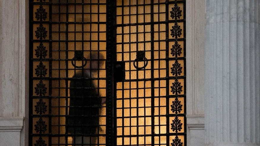 An employee of the Maximos Mansion, the Greek Prime Minister's office in central Athens, closes the door, on Monday, June 15, 2015. As concern over Greece's financial future swelled across financial markets and the two sides quarreled over who's to blame for the current standoff, Prime Minister Alexis Tsipras called an emergency meeting with his team of bailout negotiators. (AP Photo/Petros Giannakouris)