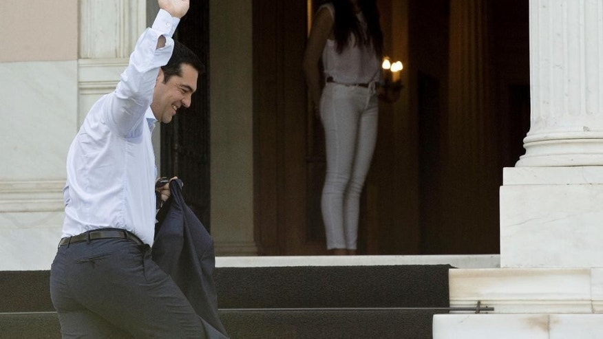 "Greek Prime Minister Alexis Tsipras waves to photographers as he arrives at his office in central Athens Tuesday, June 16, 2015. Greece insisted Monday it is ready to return to bailout talks ""at any moment"" after a breakdown in negotiations with creditors pushed the country closer toward bankruptcy and jolted international markets. (AP Photo/Petros Giannakouris)"