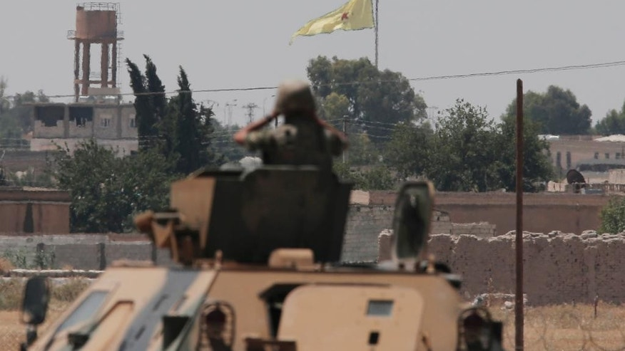 In this photo taken from the Turkish side of the border between Turkey and Syria, in Akcakale, southeastern Turkey, a Turkish soldier on an armoured personnel carrier watches as in the background a flag of the Kurdish People's Protection Units, or YPG, is raised over the city of Tal Abyad, Syria, Tuesday, June 16, 2015. Kurdish fighters with the YPG,  captured large parts of the strategic border town of Tal Abyad from the Islamic State group Monday, dealing a huge blow to the group which lost a key supply line for its nearby de facto capital of Raqqa, a spokesman for the main Kurdish fighting force said.  (AP Photo/Lefteris Pitarakis)