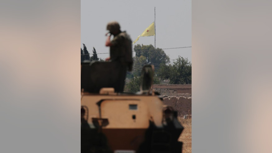 In this photo taken from the Turkish side of the border between Turkey and Syria, in Akcakale, southeastern Turkey, a Turkish soldier stands on an armoured personnel carrier as in the background a flag of the Kurdish People's Protection Units, or YPG, is raised over the city of Tal Abyad, Syria, Tuesday, June 16, 2015. Kurdish fighters with the YPG,  captured large parts of the strategic border town of Tal Abyad from the Islamic State group Monday, dealing a huge blow to the group which lost a key supply line for its nearby de facto capital of Raqqa, a spokesman for the main Kurdish fighting force said.  (AP Photo/Lefteris Pitarakis)