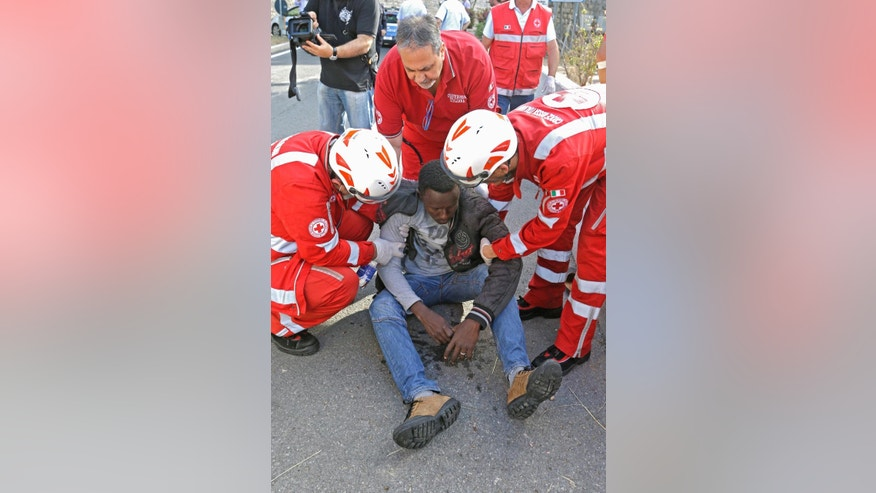 A migrant is treated by Italian Red Cross staff during his evacuation by Italian police at the Franco-Italian border near Menton, southeastern France, Tuesday, June 16, 2015. Some 150 migrants, principally from Eritrea and Sudan, have been trying since last Friday to cross the border from Italy but have been blocked by French and Italian police. (AP Photo/Lionel Cironneau)