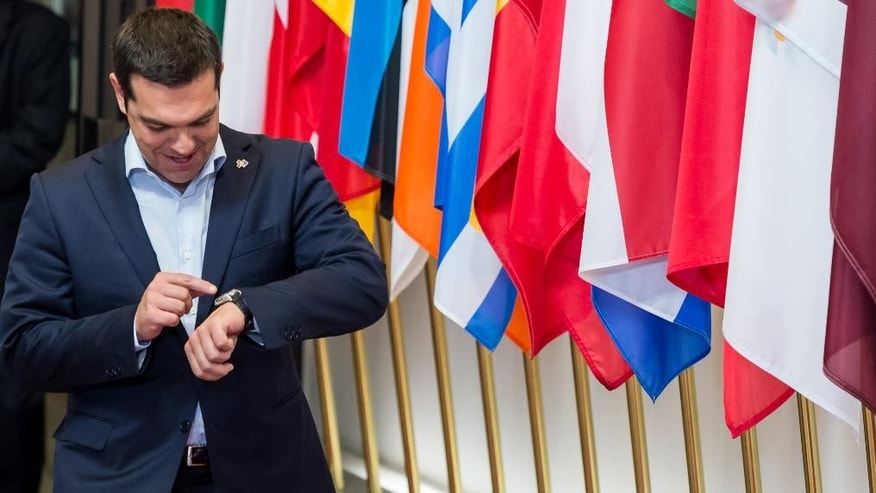 FILE - A Thursday, June 11, 2015 file photo showing Greek Prime Minister Alexis Tsipras looking at his watch as he departs the EU-CELAC summit in Brussels. Greek Prime Minister Alexis Tsipras continued his diplomatic offensive on Thursday to try to convince European creditors to pay out the bailout loans the country needs to avoid default. (AP Photo/Geert Vanden Wijngaert, File)