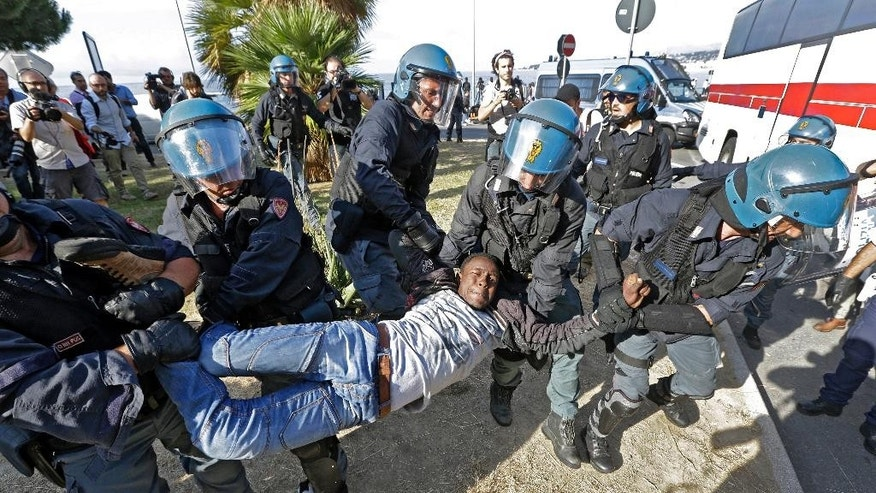A migrant is removed by Italian police at the Franco-Italian border near Menton, southeastern France, Tuesday, June 16, 2015. Some 150 migrants, principally from Eritrea and Sudan, have been trying since last Friday to cross the border from Italy but have been blocked by French and Italian police. (AP Photo/Lionel Cironneau)