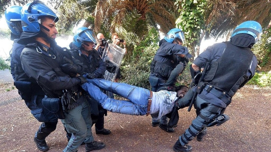 Italian police officers remove a migrant in Ventimiglia, at the Italian-French border Tuesday, June 16, 2015. Police at Italy's Mediterranean border with France have forcibly removed some of the African migrants who have been camping out for days in hopes of continuing their journeys farther north. The migrants, mostly from Sudan and Eritrea, have been camped out for five days after French border police refused to let them cross. (Luca Zennaro/ANSA via AP)