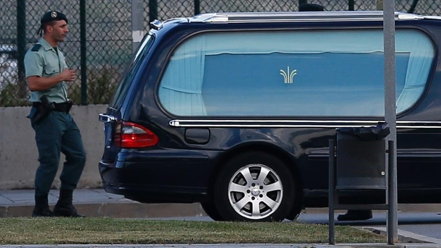 A vehicle carrying a coffin with the remains of one of the victims of the Germanwings aircraft crash leaves the Barcelona airport in Spain, on Monday, June 15, 2015. The remains of 32 Spaniards killed in the Germanwings jet crash were flown from France to Barcelona on Monday, 12 weeks after the plane's co-pilot slammed the plane into the French Alps. (AP Photo/Manu Fernandez)
