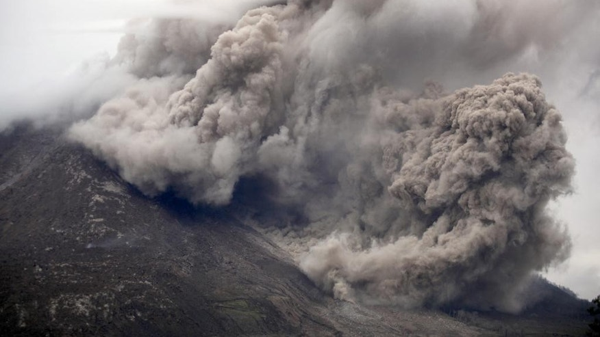 Mount Sinabung releases pyroclastic flows as seen from Tiga Serangkai, North Sumatra, Indonesia, Tuesday, June 16, 2015. Authorities have been closely monitoring Sinabung since June 2 when its status was raised to the highest alert level due to the growing size of its lava dome. (AP Photo/Binsar Bakkara)
