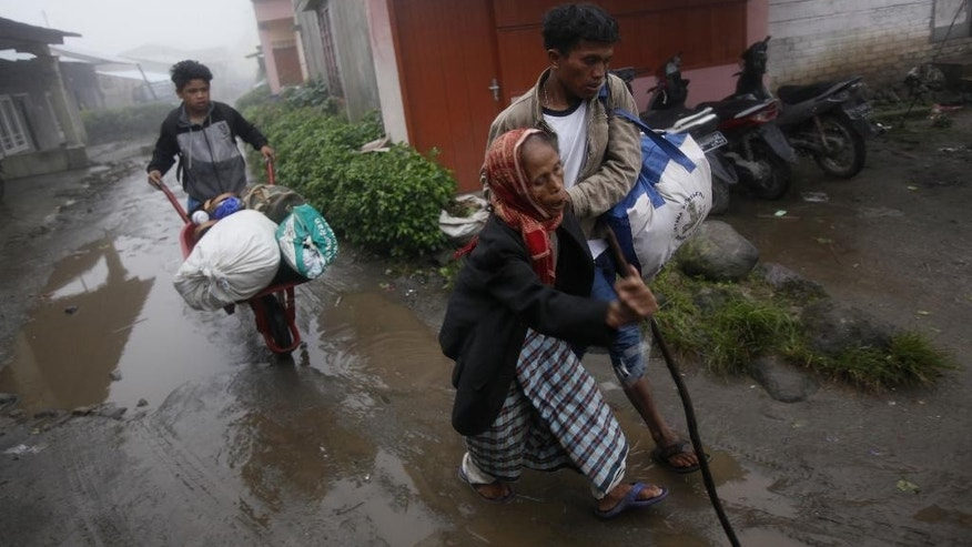 Villagers carry their belongings as they are evacuated from their homes on the slope of Mount Sinabung in Kuta Tengah, North Sumatra, Indonesia, Monday, June 15, 2015. Authorities evacuated hundreds of villagers living near the volcano that is spewing hot ash down its slopes almost daily. (AP Photo/Binsar Bakkara)