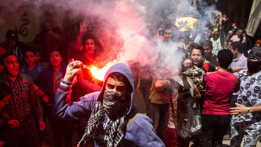 In this April 24, 2015 file photo, an Egyptian youth carries a lit flare as supporters of the Muslim Brotherhood gather in the El-Mataria neighborhood of Cairo, Egypt, to protest the 20-year sentence for ousted president Mohammed Morsi and verdicts against other prominent figures of the Brotherhood.